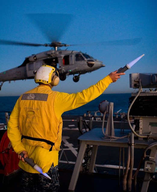 Boatswain's Mate Second Class (SW) Lucky Hughes directs an SH-60S during deck landing qualifications onboard USS Milius