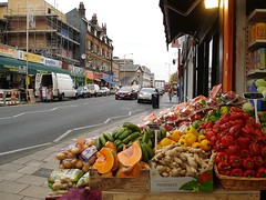 A view along a road with shops on both sides.  The road runs diagonally across the frame from bottom left, and the bottom right half of the photo is taken up by a display of vegetables in the foreground including ginger root, yellow and red peppers, and unripe plantains.  Some of the buildings across the road from this have scaffolding up.