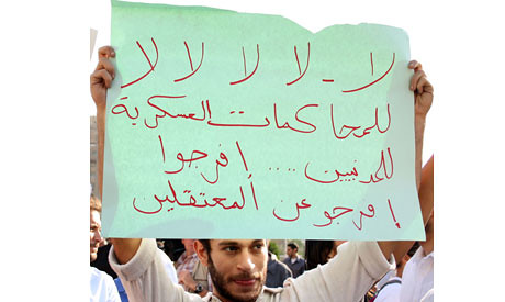 "Demonstrator holds sign saying ""No Military Trials"" in a rally that opposed the new decrees by President Morsi. Demonstrations have occured everyday since November 22. by Pan-African News Wire File Photos"