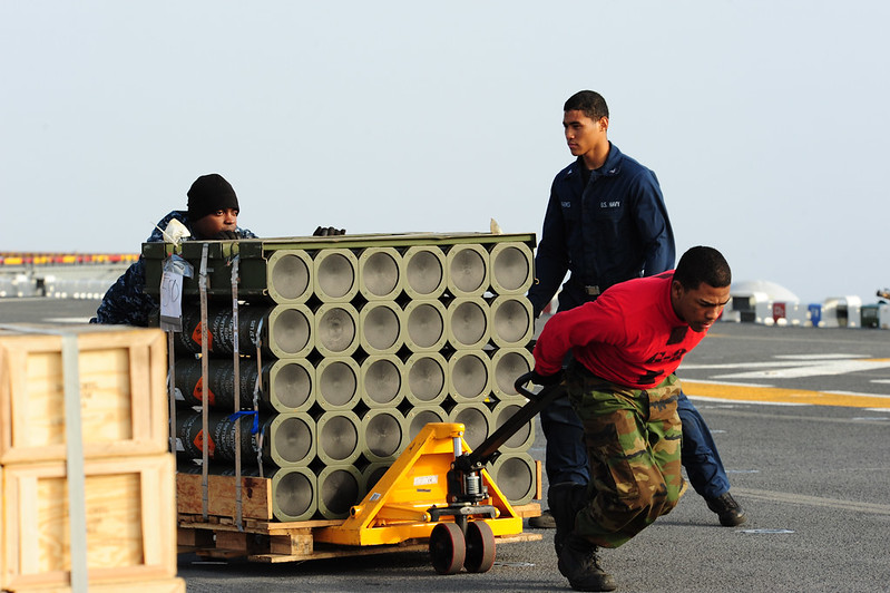 Sailors aboard USS Boxer (LHD 4) move ordnance on the flight deck