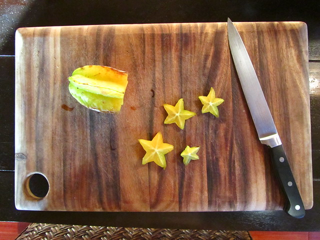 Sliced Starfruit on a cutting board, with knife.