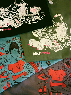 Photo of four t-shirts folded and sitting on top of each other. Black tee shows an imprint of a chicken knitting with a computer and several balls of yarn sitting around them. Olive green tee also shows the knittin' chicken. Blue tee shows a woman with a beehive hairdo sitting on a stool knitting with a toddler next to her. They're surrounded by little teacups, candles, a typewriter, and assorted knick-knacks. A brown tee shows that same illustration.