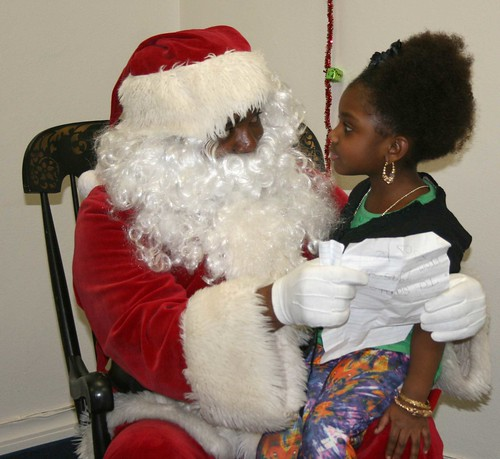 Four-year-old Zyazia Hill reviews her Christmas list with Santa at the 15th Annual South Side Christmas Tree Lighting Ceremony at the Beauchamp Library in Syracuse.     ITC Media