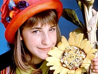 A season one photo of Blossom wearing a straw hat and cuddling up to a sunflower.