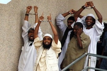 Four Sudanese convicts lift their handcuffs as they are escorted out of the courtroom in the capital Khartoum, June 24, 2009. Four Sudanese men were on Wednesday condemned to hang for killing a U.S. aid official and his driver in Khartoum. by Pan-African News Wire File Photos