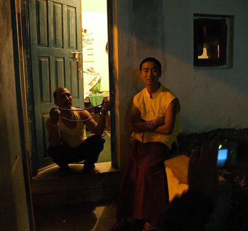 Night Watch of TV; Tharlam Monastery guard with a large mala in the open door, and a Tibetan monk friend at night on Sachen Kunga Nyingpo's memorial, Guardhouse, Sakya Lamdre, Tharlam Monastery of Tibetan Buddhism, Boudha, Kathmandu, Nepal by Wonderlane