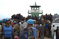 Government police arrive on a boat at goma port as U.N. peacekeepers watch on. Credit: William Lloyd-George/IPS