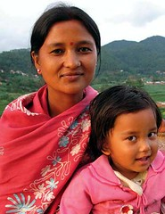 An indian woman and child pose  in front of the mountains.