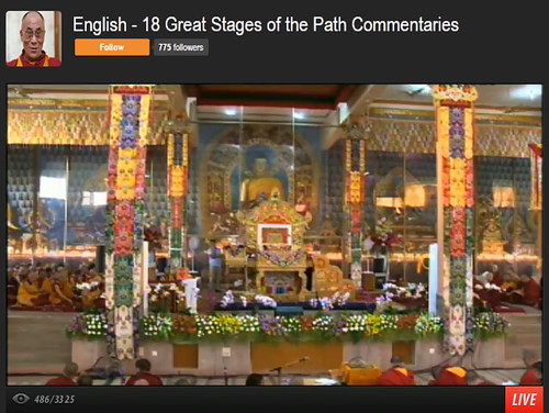 His Holiness the 14th Dalai Lama's throne, with traditional decorations, flowers, statue of Lord Buddha, 18 Great Stages of the Path Commentaries, webcast interface, Dharamasala, India by Wonderlane