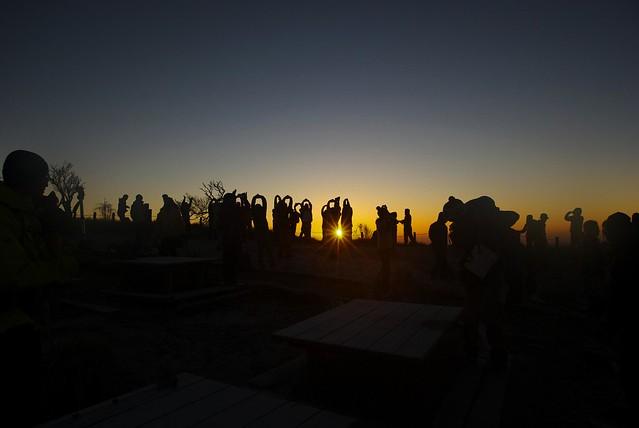 蛭ヶ岳山頂でご来光を背に準備体操をするツアー客