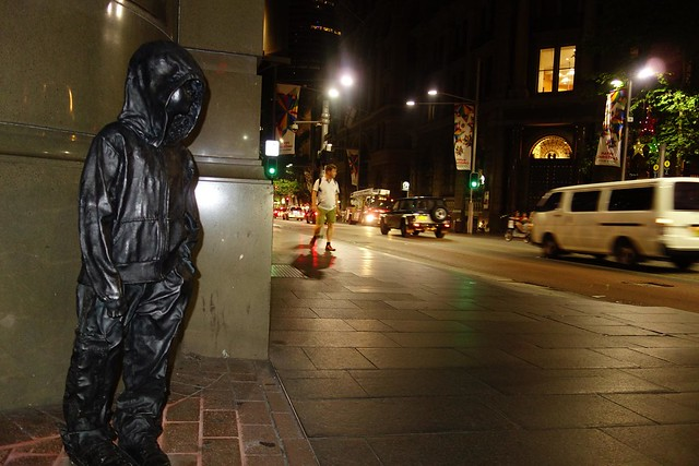 hooded little boy statue looks onto Sydney night time street traffic