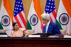 U.S. Secretary of State John Kerry acknowledges Indian Minister of External Affairs Shushma Swaraj before addressing reporters during a news conference on August 30, 2016, at the Jawarhalal Nehru Bhawan in New Delhi, India, following the annual U.S.-India Strategic and Commercial Dialogue also attended by U.S. Commerce Secretary Penny Pritzker and Indian Commerce Minister Nirmala Sitharama. [State Department Photo/ Public Domain]