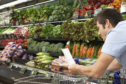 A young dad checks his shopping list as he passes by the produce section of a grocery store. With nearly one third of children in America at risk for preventable diseases, proper nutrition early in life can help set the stage for healthier dietary and lifestyle habits and future success in school.