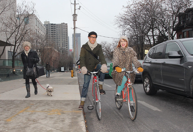 Young couple riding bikes during fall on city street