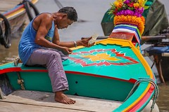 A sea gypsy fisherman from the village of Chao Leh on the island of Koh Lanta, Thailand paints his boat with designs meant to bring good luck during the upcoming season in the Andaman Sea. #travel #Thailand #amazingthailand