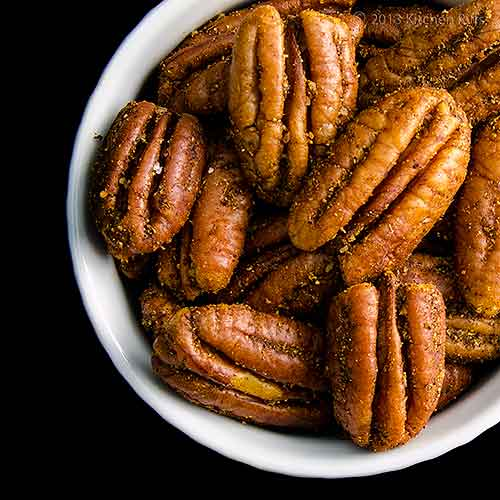 Spiced Roasted Pecans in White Ramekin, Overhead View on Black