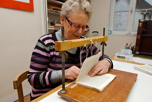 Jocelyne travaillant sur la reliure d'un livre