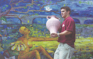 Art student Ryan Hattersley '01 carrying a completed ceramic pot past a mural outside Pomona's sculpture studio in a spring 2000 Pomona College Magazine article.