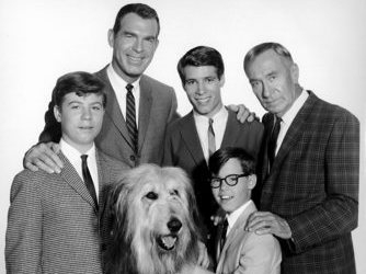 The original cast of My Three Boys, including dad, grandpa and shaggy dog, stand in a clean-cut 1950s black and white tableau, mostly smiling.