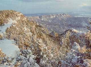 From an altitude of two miles in the Cibola National Forest, a snow-touched landscape lays below. Copyright © 2001 Sandia Crest Byway.