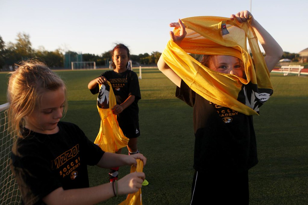 JAIME HENRY-WHITE/Missourian  Ella Thompson(cq), 8, right, puts on a practice jersey during a three-on-three practice scrimmage during a soccer clinic run by the MU women's soccer team Monday Sept. 10, 2012 at Walton Stadium.