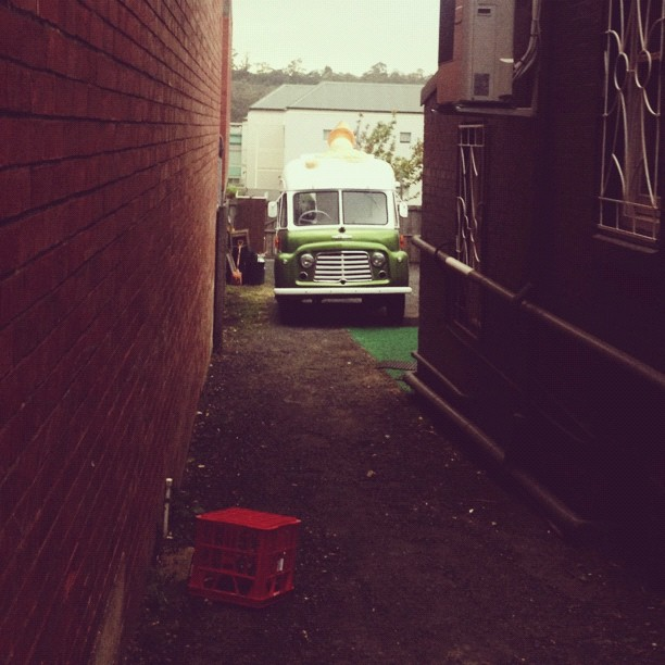 An old ice cream truck hiding in an alleyway.