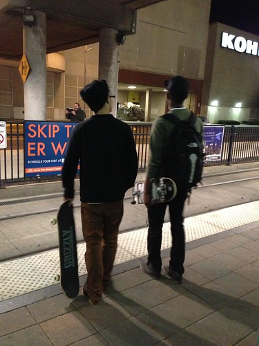Two skateboardres, watching the light rail preacher