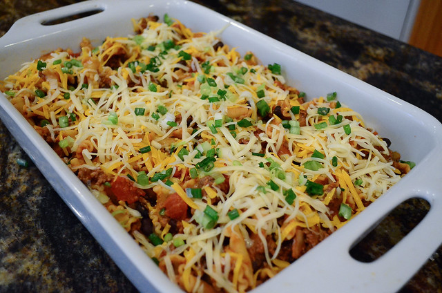 The mixture is transferred to a baking pan and cheese and green onion are added on top.