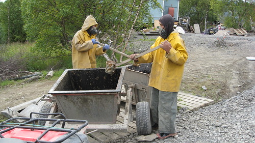 Wearing breathing apparatus, Alaska village residents transfer human waste to a collection bucket.  The untreated waste will then be taken to a sewage lagoon. Working with its partners, USDA is funding projects to replace these systems with safe sewage handling systems, reducing the incidence of disease in Alaska rural villages.