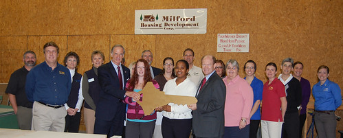 A key to home ownership:  Senator Tom Carper (center left) and  Senator Christopher Coons (center right) with Self-help participant Erin Moyer, and Self-help homeowner Latonya Smith.  Joining them are staff from USDA and Milford Housing Development Corp. Photos courtesy of Sen. Carper's office.