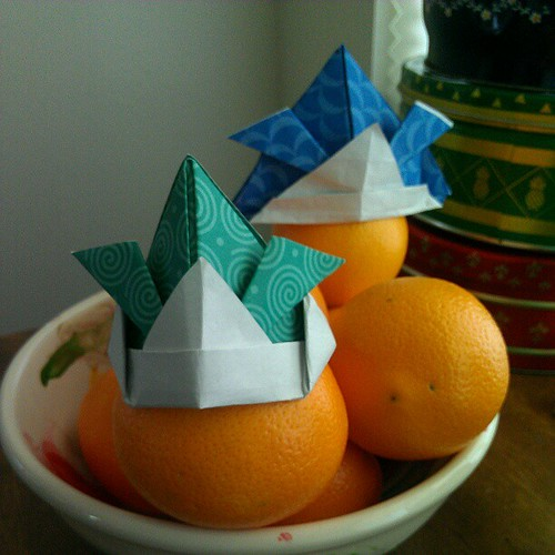 Annalie found my origami book & paper. She folded the blue hat first, then the green hat.