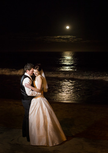 Bride and groom at the beach with a full moon.