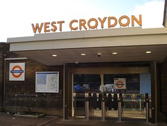 "A back entrance to a railway station, leading directly onto one of the platforms. Three ticket gates (including a wide, accessible one) stand between the viewer and the platform. An information board is to the left of the entrance, along with a London Overground roundel. Freestanding letters on top of the entrance read ""WEST CROYDON""."