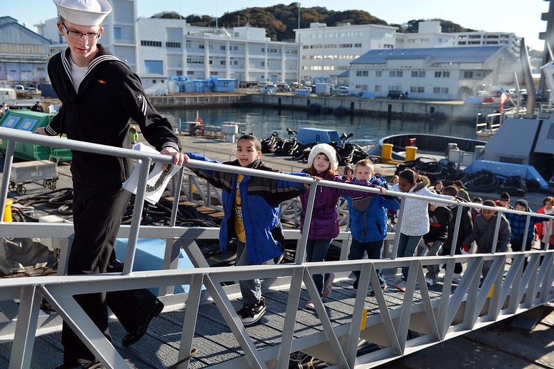 Seaman Apprentice Ryan Aker leads students from Ikego Elementary School onto USS McCampbell