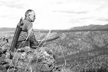 Aldo Leopold seated on rimrock above the Rio Gavilan in northern Mexico while on a bow hunting trip in 1938. (Photo courtesy Aldo Leopold Foundation)