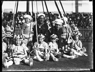 Two United States sailors with children around a maypole possibly at the Vice-Regal Garden Party