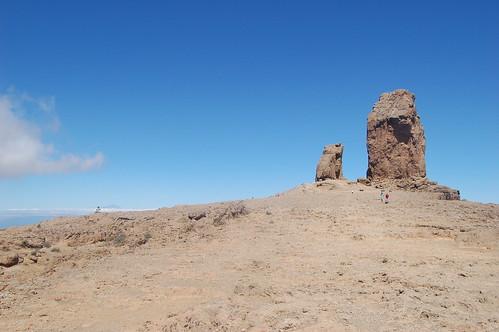 Von weitem der Roque Nublo, vorne sind zwei kleine Wanderer