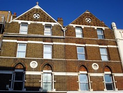 Three upper floors of two terraced buildings.  The brickwork is exposed, included pointed arches above the first-floor windows.  There is a circular moulding between each pair of first-floor windows.  The roof profile is pointed, and the left-hand one has a fairly generic finial on top.