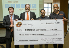 The 5th annual App Competition sponsors and staff from the Technology Development Center (TDC) and App Center, a part of the TDC, shared a check mockup showing competition prize money. Pictured are (from left) Steve Price, TDC director; Ron Van Den Bussche, associate vice president for research; Jai Rajendra, App Center manager; and Craig Watters, Riata Center director.
