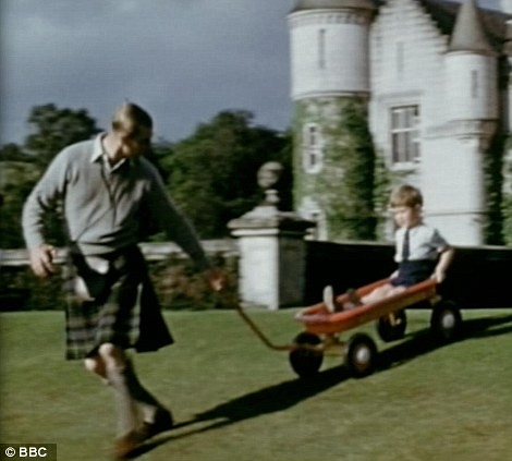 1951 Dressed in a kilt, Prince Philip pulls a young Prince Charles down a slope in a toy cart at Balmoral, before having a go himself1