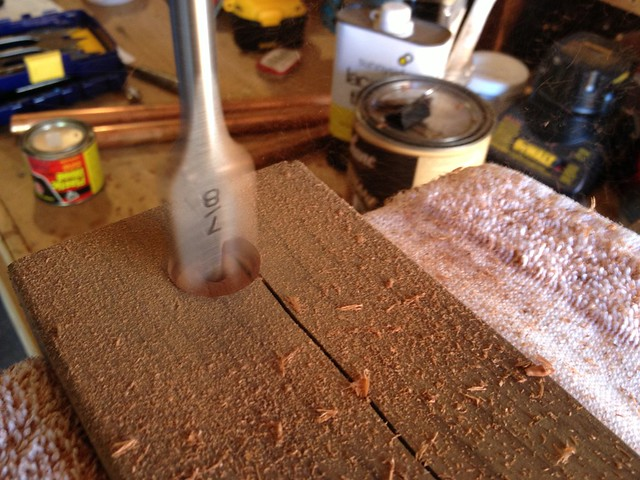 Drilling out insets for copper pipe that will hold lower shelf