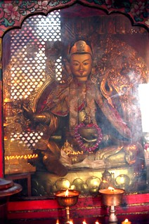 Statue of Padmasambhava, lotus born guru, gilded metal, incense, ornate silks surrounded by candle offerings, stupa, dorje, kapala scullcup bowl with nectar, khatvangha (tantric trident), shrine, Swayambhunath, Nepal in 1993