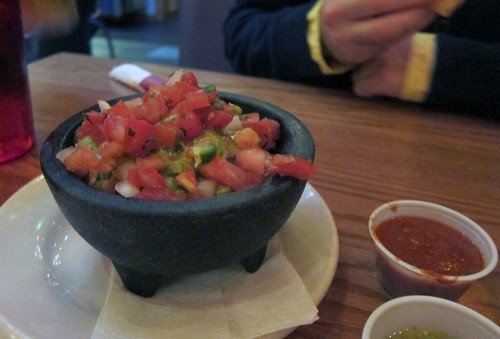 Squat cast-iron bowl of guacamole topped with diced tomatoes.
