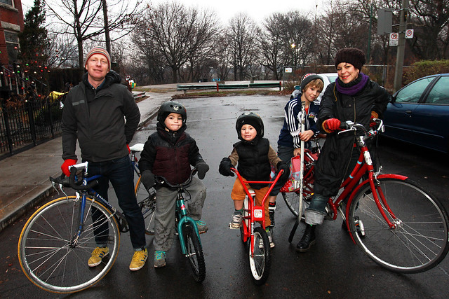 Family dressed up warm for fall weather in wet street standing with their bicycles