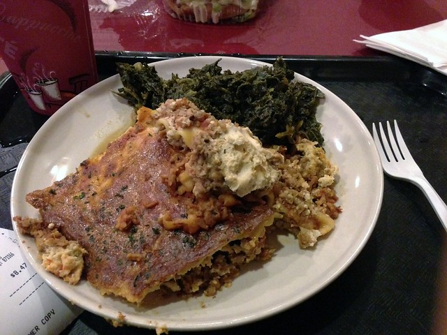 Plate with a large piece of lasagne and a side of collard greens.