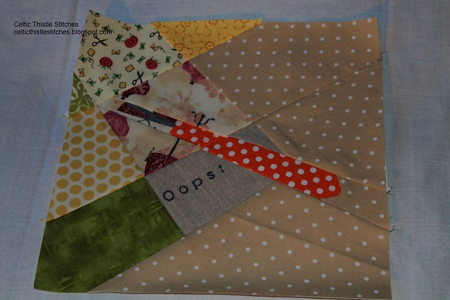 paper-pieced quilt block showing a seam ripper about to be used to correct an error in the sewing of the block