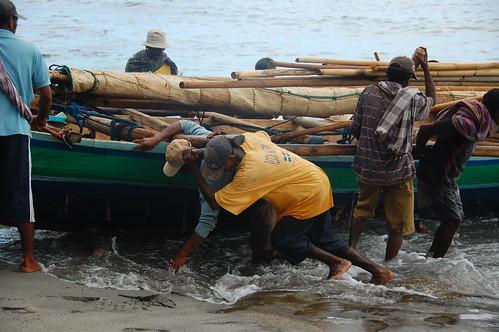 Men push hunting boat to shore