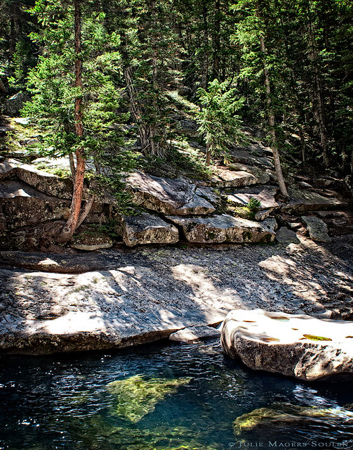 The Roaring Fork River is banked by rocky granite outcrops and a woodland pine forest.