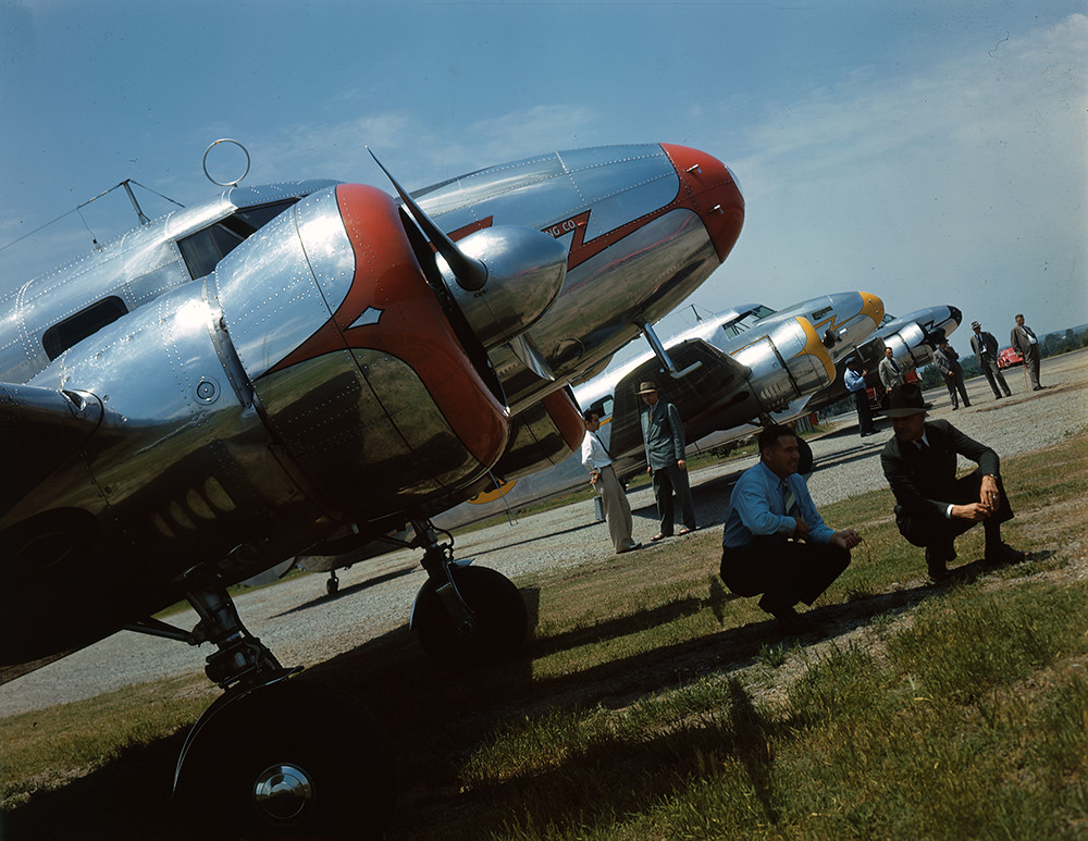 [Men in front of Lockheed 12A Electra Junior Airplanes]