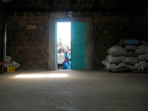 Children stare into the almost empty food bank during a town meeting. Nyaururu, Kenya